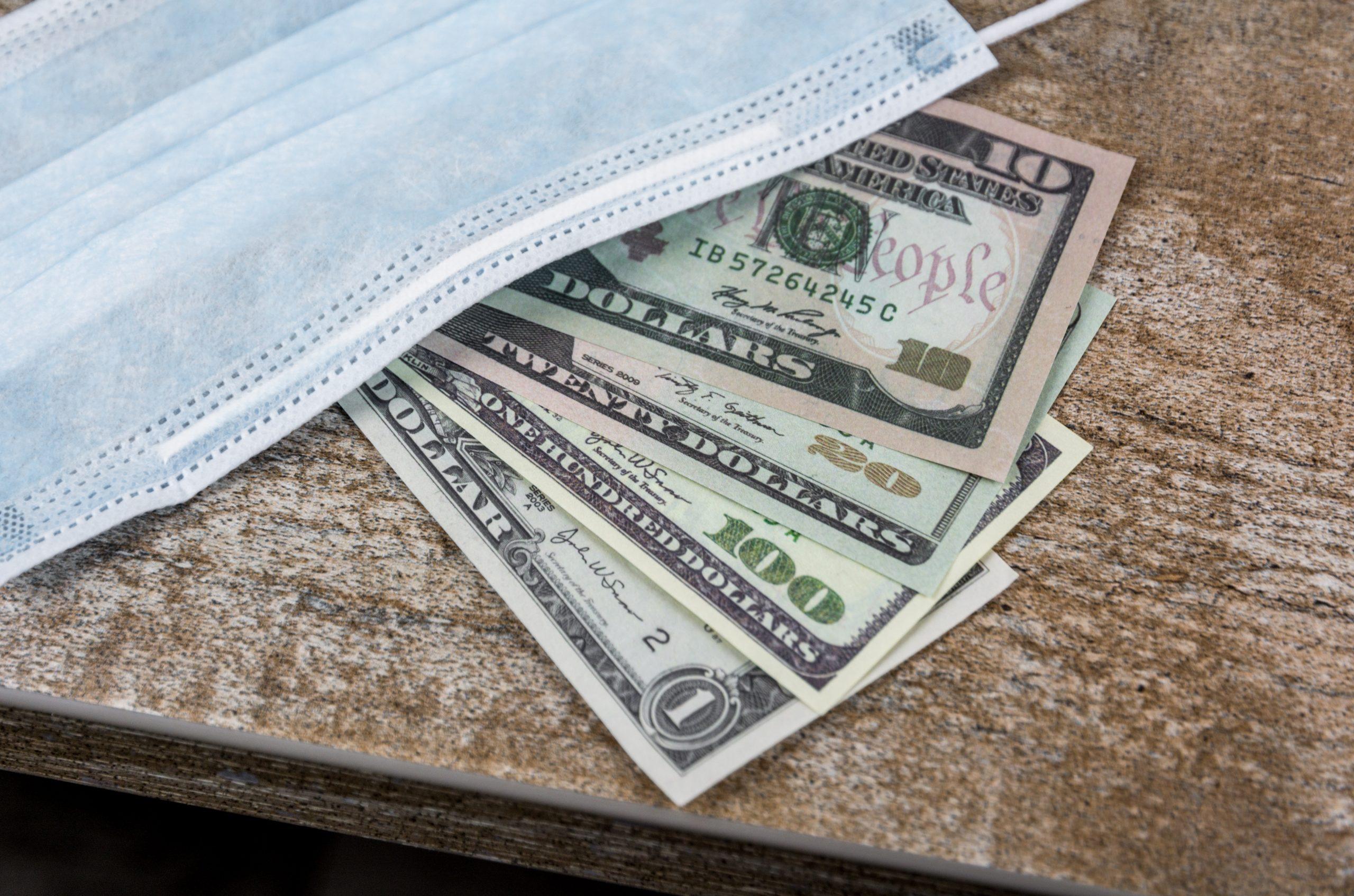 dollar bills beneath a medical mask