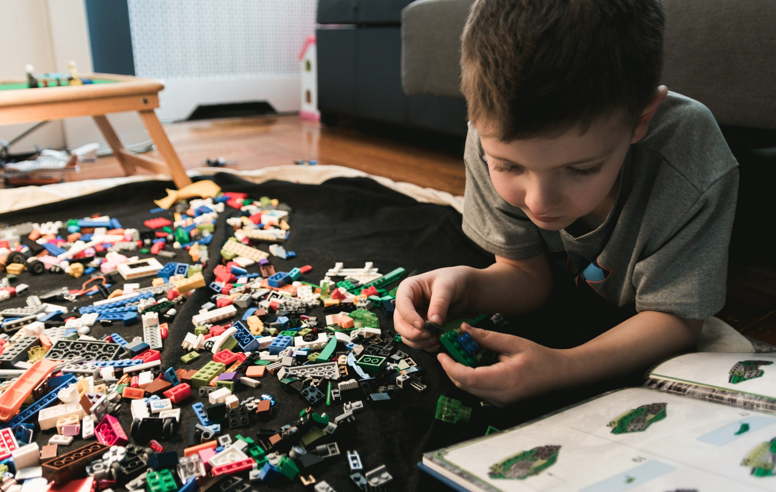 kid lays on belly on floor reading lego manual with legos all about